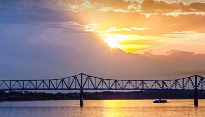 Bridge spanning a large river at sunset